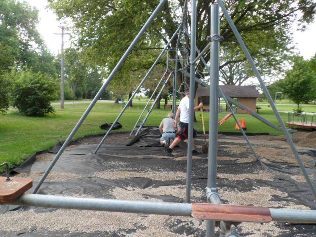 Crew laying new gravel at playground at Plover City Park