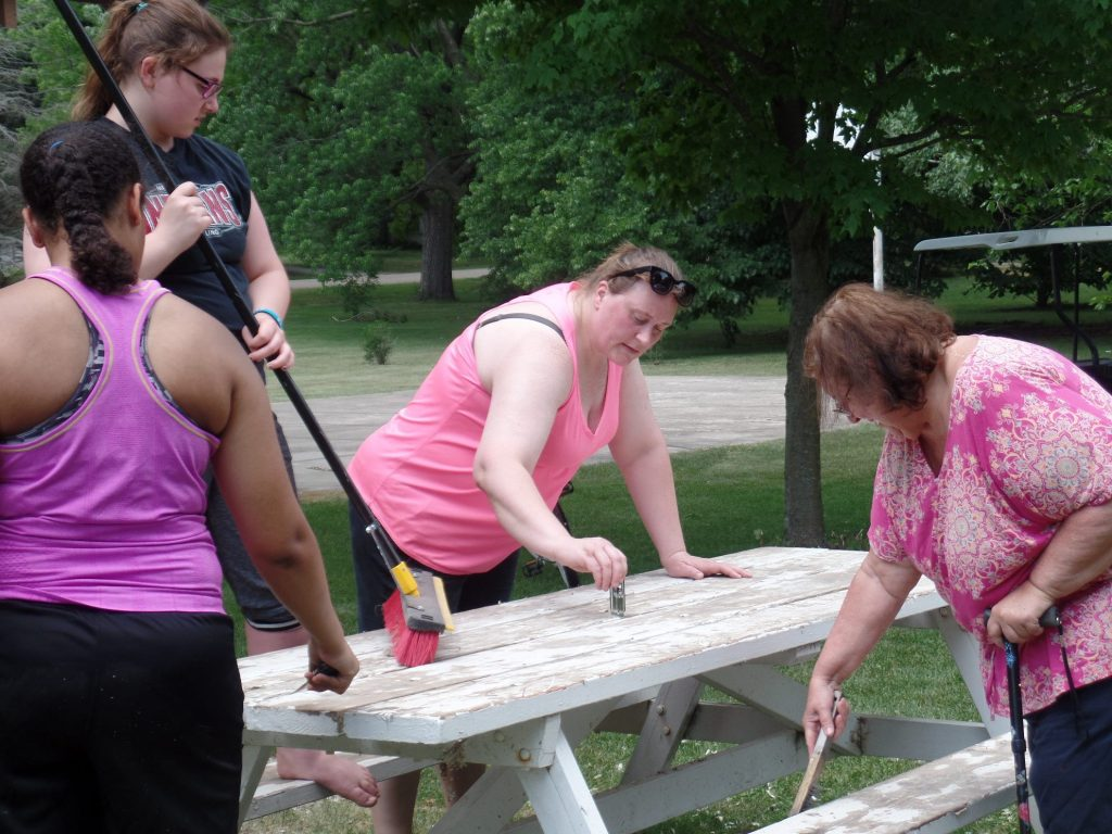 Volunteers painting picnic table at Plover City Park