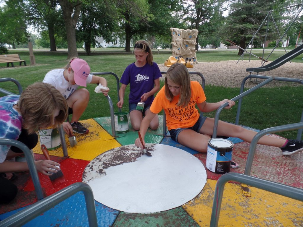 Volunteers painting playground equipment at Plover City Park